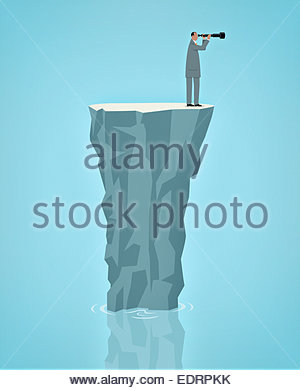 Businessman stranded alone on rock in ocean looking through telescope - Stock Photo