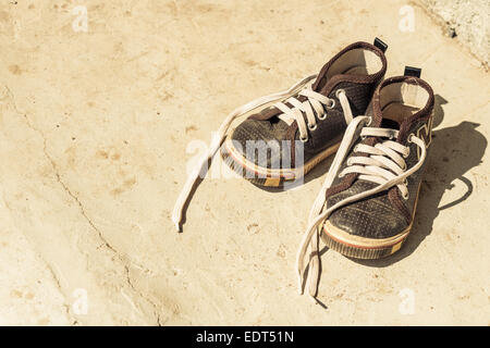 Kid's old canvas shoes in front of rural house ,Thailand - Stock Photo