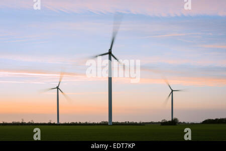 Modern wind turbines in field, previously RAF WW2 airfield, at sunset on a fine winter evening. - Stock Photo