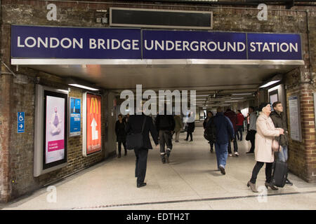 London, UK. 09 Jan 2015. Passengers leave London Bridge station and look at a sign warning of proposed travel disruption - Stock Photo