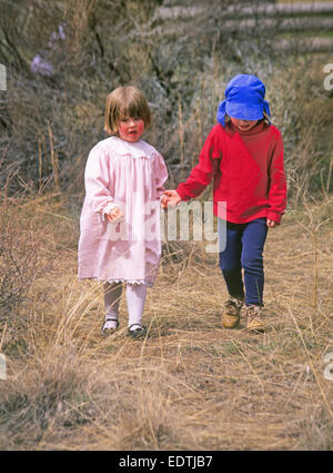 Two young girls hold hands as they walk through a field. - Stock Photo