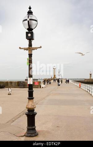 UK, England, Yorkshire, Whitby, visitors walking along West Pier to lighthouse - Stock Photo