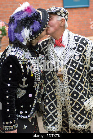 A Pearly King and Queen kiss each other before the Harvest Festival service.at St. Paul's Church, Covent Garden. - Stock Photo