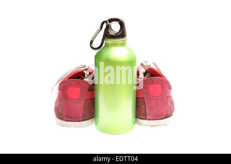 green metal bottle for drinks with sport shoes - Stock Photo