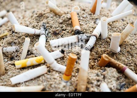 many burnt cigarettes on ashtray and sand - Stock Photo