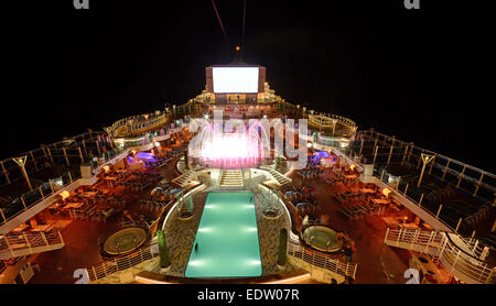 Cruise ship deck illuminated at night in open waters - Stock Photo