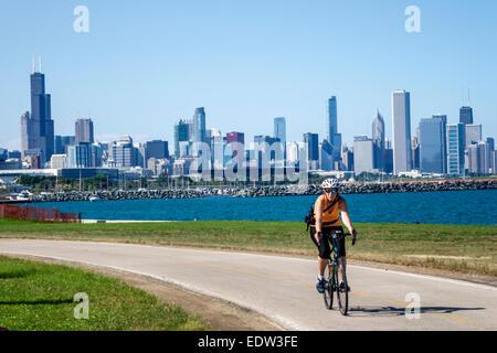 Chicago Illinois South Side Lake Michigan 39th Street Beach Lakefront Trail woman biker bicycle riding city skyline - Stock Photo