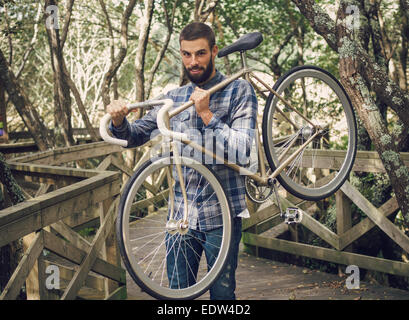 Hipster man holding his bicycle in a park outdoors - Stock Photo