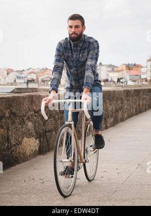 Hipster man riding in a fixie bike in the city. - Stock Photo