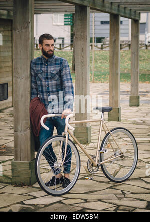 Hipster man with a fixie bike in a park outdoors - Stock Photo