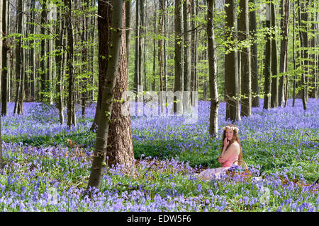 Innocent young woman with pink fairy dress in a springtime bluebells forest - Stock Photo