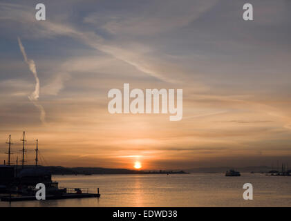 Low yellow winter sun setting in SW, Oslo fjord Norway, vapour trails in  sky, sailboat rig and masts silhouetted - Stock Photo