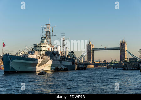 Moored by Tower Bridge, HMS Belfast is a Royal Navy light cruiser and a museum ship in London - Stock Photo