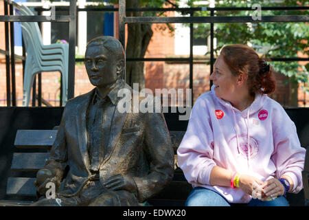 Woman sits down beside the statue of Alan Turing in Sackville Gardens, Manchester. - Stock Photo