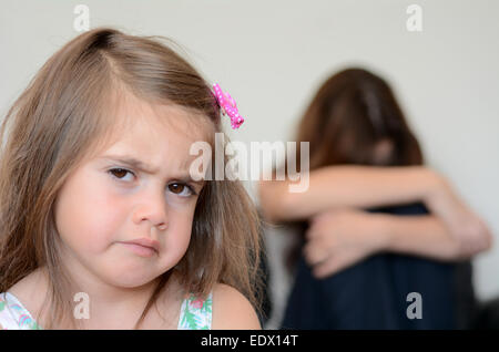 Little girl (age 05) having a temper tantrum with her desperate mother in background - Stock Photo