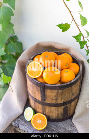 bucket of oranges, with sackcloth, on an old wooden bench against ivy covered white wall - Stock Photo