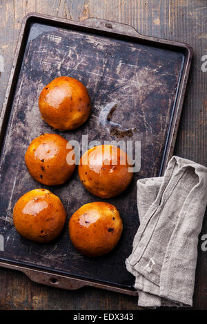 Homemade buns with raisins on Old scratched black dark tray - Stock Photo