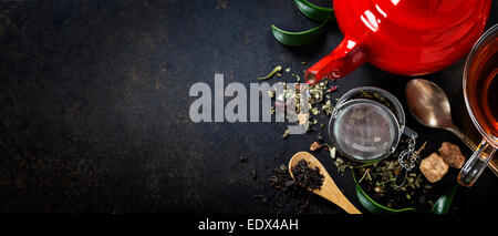 Tea composition with red teapot on dark background - Stock Photo