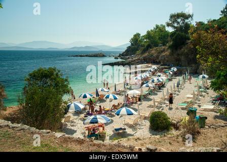 Kassiopi Beach, Corfu Island, Greece. Tourists relaxing on beautiful beach of Kassiopi in the north area of Corfu - Stock Photo