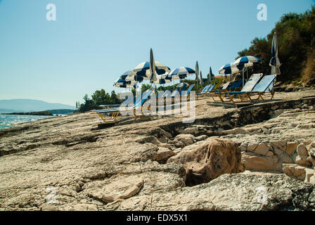 Sunbeds and umbrellas (parasols) on the beach in Corfu Island - Stock Photo