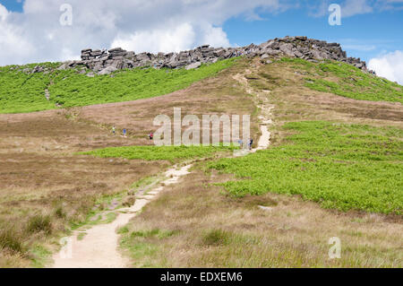 Path leading up to Higger Tor with many people on and around the rocks. Peak District, Derbyshire. - Stock Photo