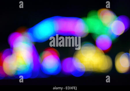 Flashing multicolored lights that were blurred by zooming the camera lens during exposure produced this unusual - Stock Photo