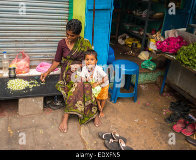 THANJAVOUR, INDIA - FEBRUARY 14: An unidentified child and a woman in traditional Indian attire are sitting. Woman - Stock Photo