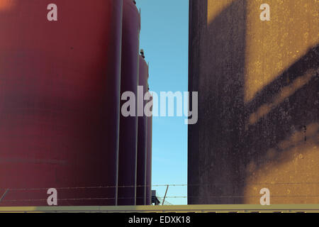 Red tanks close to wall against blue sky. Fence with barbed wire - Stock Photo