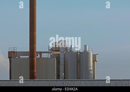Tanks for storing food oils loom against the bleak sky, the chimney reaching even higher - Stock Photo