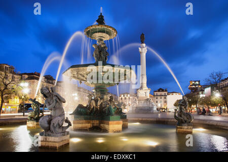 Fountain on Rossio Square at night in Lisbon, Portugal. Baroque style artwork with mythical creatures sculptures. - Stock Photo