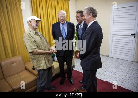 Alan Gross greets Patrick Leahy, D-Vt., Sen. Jeff Flake, R-Az., Sen.and Rep. Chris Van Hollen, D-Md. at an airport - Stock Photo