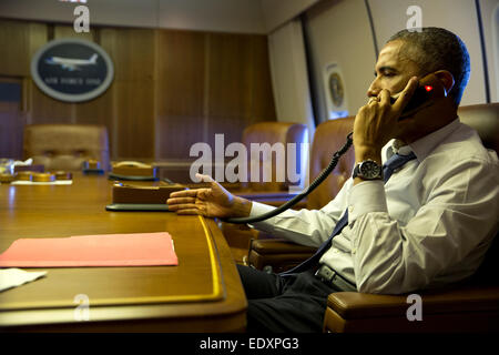 President Barack Obama talks on the phone with French President Francois Hollande from aboard Air Force One, Jan. - Stock Photo