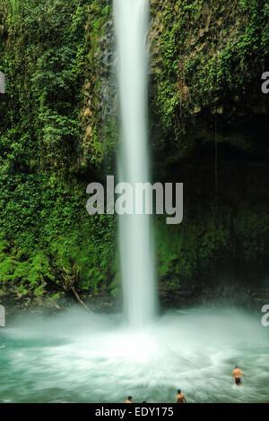 Tourists swimming in a waterfall near La Fortuna, Costa Rica.
