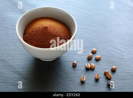 Ground coffee in a bowl, slate background - Stock Photo