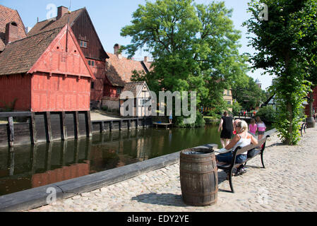 Visitors beside a small river  in the Old Town open-air living museum ( Den Gamle By ) in Aarhus, Denmark's second - Stock Photo
