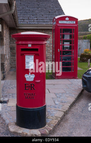 Close-up of 2 British icons - traditional post box & bright red telephone box or kiosk, amenities in Bolton Abbey - Stock Photo