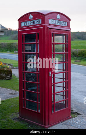 Close-up of traditional bright red telephone box or kiosk standing by country lane, an amenity in Bolton Abbey village, - Stock Photo