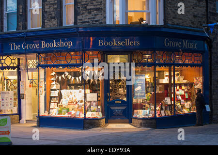 With a golden glow of lights, The Grove Bookshop looks warm & welcoming & man outside looks at window display - - Stock Photo