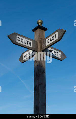 Signpost showing directions to the north, south east and west. - Stock Photo