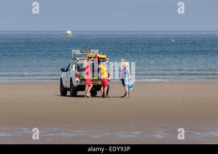 2 male RNLI lifeguards standing by 4x4 patrol vehicle talking & giving advice to a couple of holidaymakers - Whitby - Stock Photo