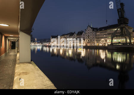 Zurich, old city buildings reflected in the river Limmat seen from a covered walkway. - Stock Photo