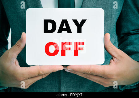 a young businessman showing a signboard with the text day off written in it - Stock Photo