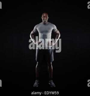 Full length image of happy young man standing on black background. Muscular African athlete in sportswear. - Stock Photo