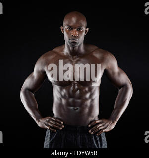 Portrait of a strong afro-american man showing off his physique against black background. Shirtless male model posing. - Stock Photo