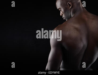 Rear view of young man with muscular build standing on black background. African shirtless male model with copy - Stock Photo