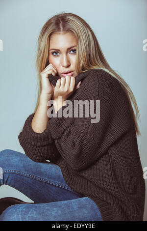 Pretty young woman sitting on floor wearing sweater. Attractive woman looking at the camera against white wall. - Stock Photo