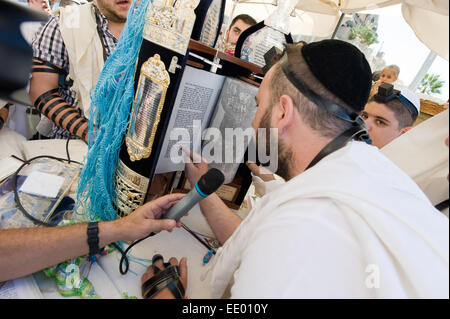 A jewish man is reading from the torah during a Bar Mitzvah ritual at the Wailing wall in Jerusalem - Stock Photo