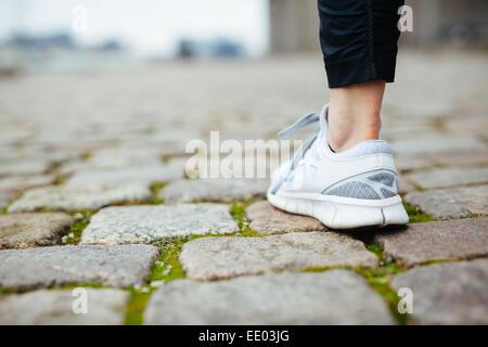 Leg of female jogger walking on pavement. Focus of shoes. Woman feet on sidewalk. - Stock Photo