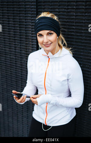 Portrait of attractive young woman listening to music on mobile phone. Female runner relaxing after a training session. - Stock Photo