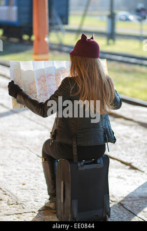Woman on baggage looking map and dont understand - Stock Photo